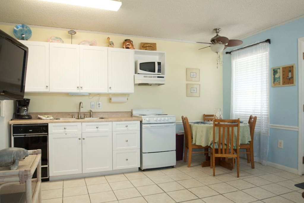 Fully stocked kitchen / dining area with stove, microwave, dishwasher, coffee maker and refrigerator