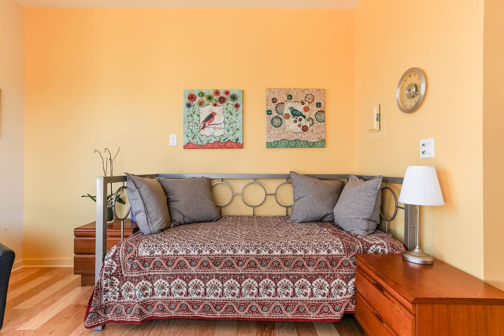 Relax and enjoy the East side of Austin. Living area with day bed / trundle (sleeps 2 here); sliding door looks out to deck with room darkening blinds.