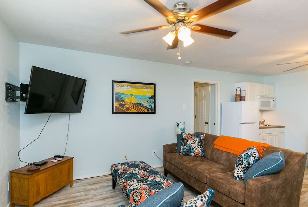"""A wall-mounted 49"""" TV with cable in the welcoming living room."""