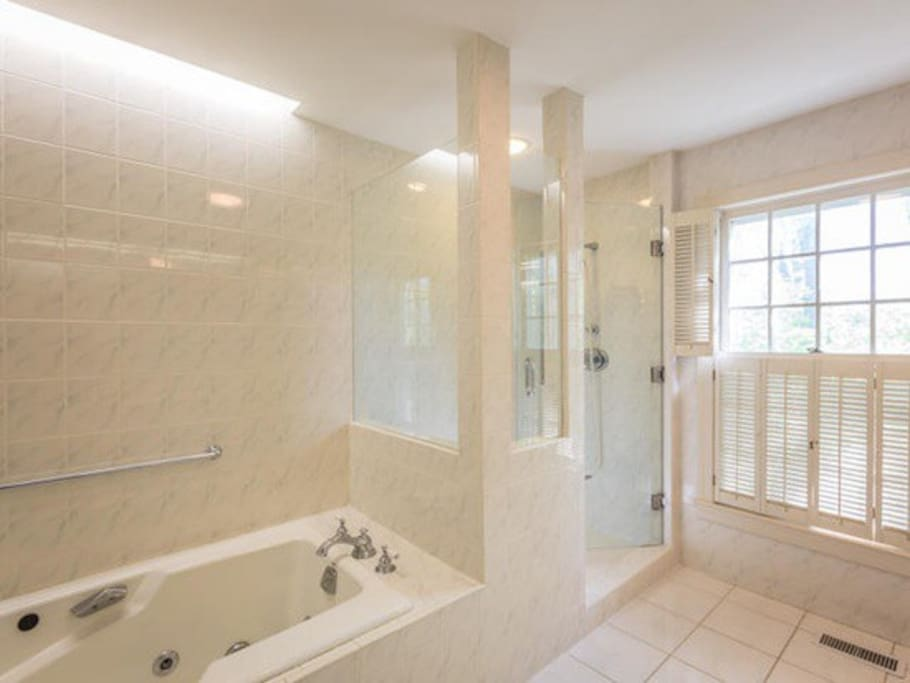Luxurious master bath with soaking tub and walk in shower, monogrammed robes .