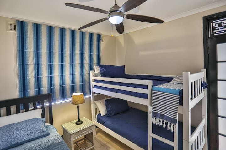 The third bedroom with a single bed and double bed. This room has a ceiling fan.