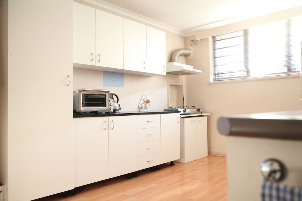 Shared Kitchen with twin gas stove, bench top oven, microwave, electric wok, frying pan, pots, fridge with freezer, cutlery, coffee mugs and glasses.