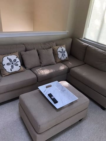 """Large """"L-Shaped"""" couch is brand-new with matching throw pillows and foot rest."""