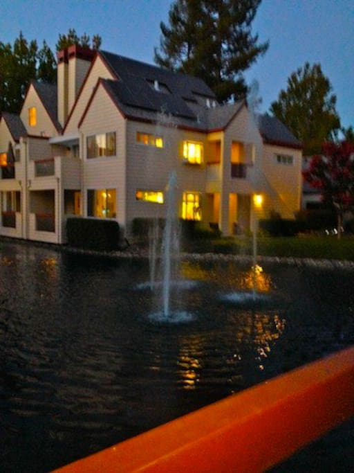 Twilight outside/front deck onto pool with soft fountains.