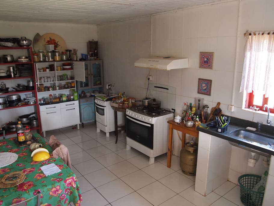 Cozinha disponível para hóspedes com fogão, geladeira, louças, talheres e copos