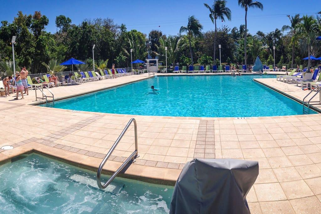 Large swimming pool with hot tub a tub & tiki bar.