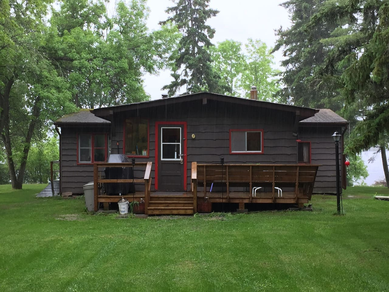 Cottage from the backyard with deck and BBQ. Great for morning coffee and bird watching.