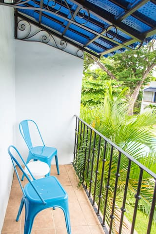 Master Bedroom balcony facing pool with chairs