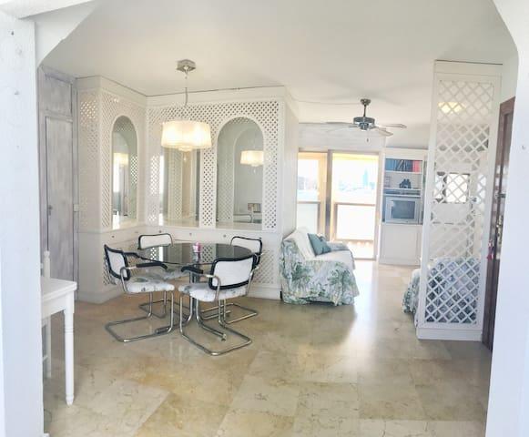 Salle à manger au 1er plan et coin salon au 2ème plan qui abrite 2 armoires avec lit incorporés invisibles en journée et s'ouvrent le soir au couché.  Des canapés du salon, vous profiterez de la vue mer avec accès direct en terrasse.