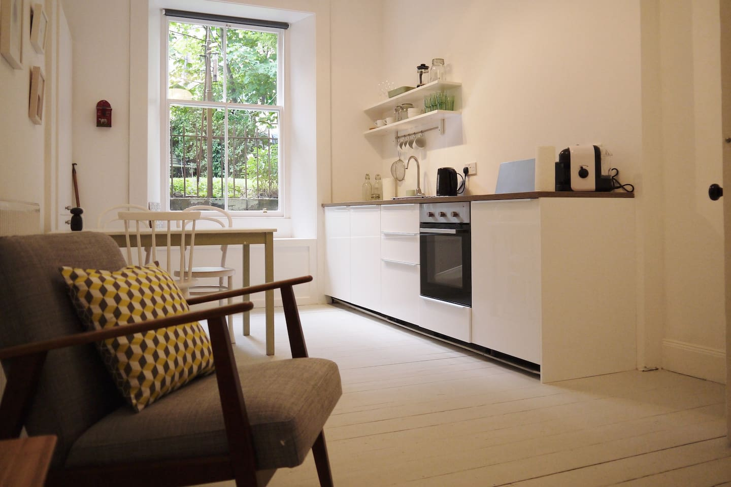 Clean, white kitchen. Lovely view to the garden.