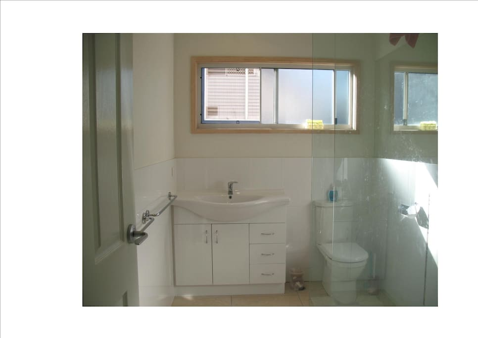 Sunny, spacious, modern two pak bathroom with large glass shower