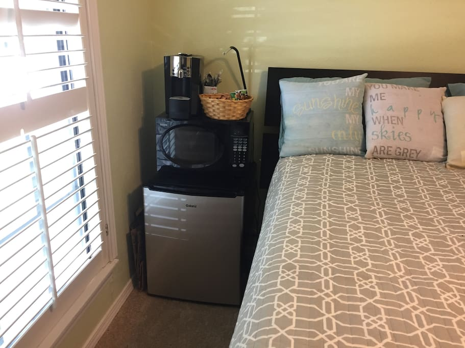 Guest bedroom is furnished with mini-fridge, microwave, and coffee maker