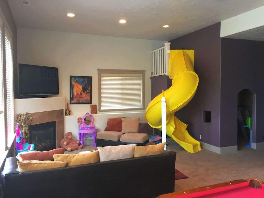 Fun family room in basement with kid`s slide, sectional, TV, and fireplace