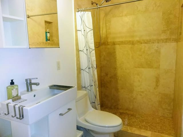 Master bathroom with stand up shower. Washer and dryer are in the master bathroom. We provide bath towels, soap, shampoo, body wash, and toilet paper.