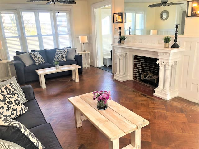 """Large living room, grand fireplace, 50"""" flat screen, and two openings to the attached sunroom with ocean views"""