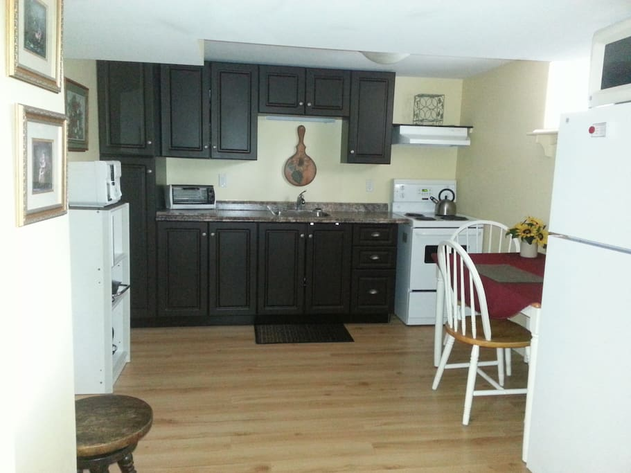 fully outfitted kitchen includes microwave, coffee maker, toaster oven, blender, fridge and stove