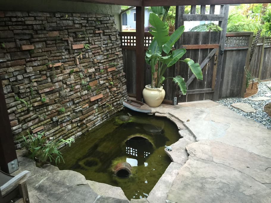 Entry is accented with koi pond, grotto wall, flagstone walkway covered by redwood lattice patio cover.