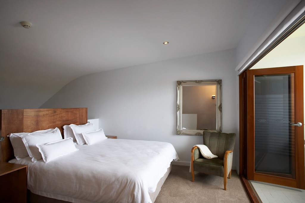 Very comfortable king sized bed with beautiful linen, bi-fold doors open on to balcony