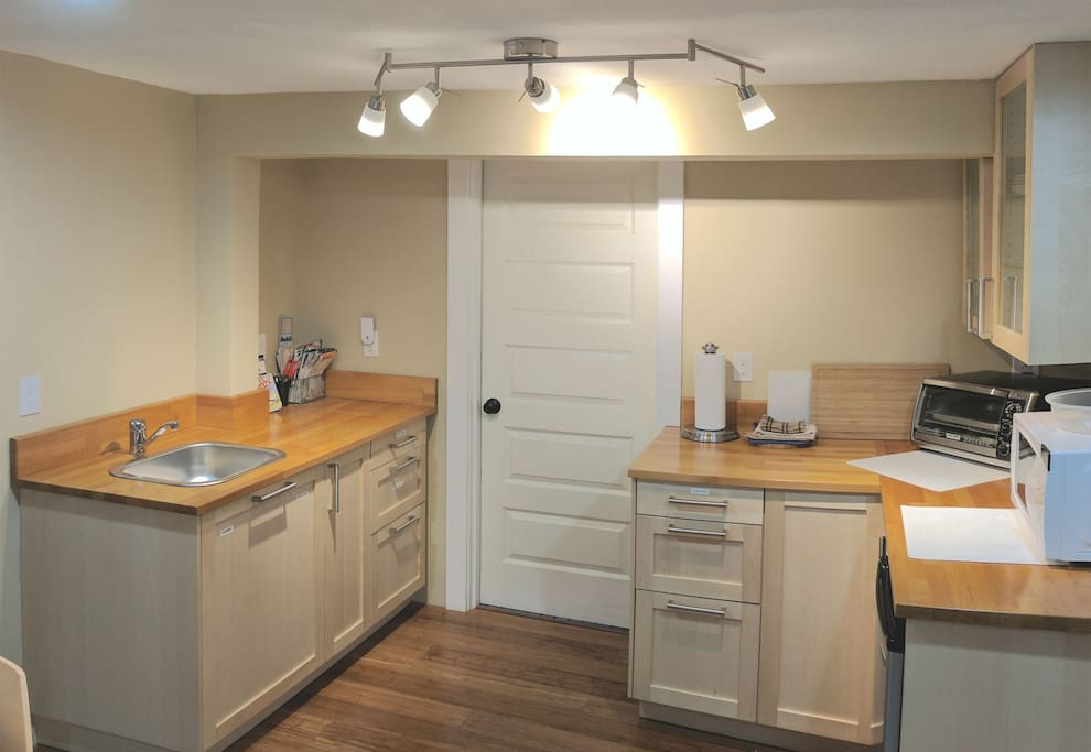 Kitchenette with sink, microwave, toaster oven, & refrigerator.