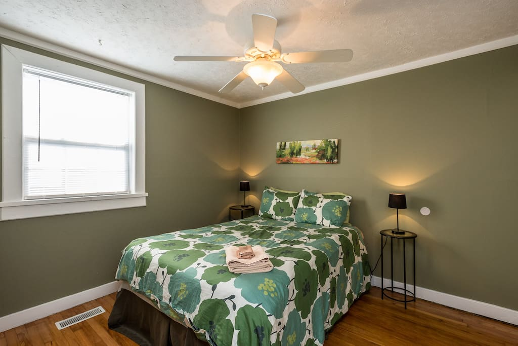 The 1st bedroom offers a queen-size bed and green decor
