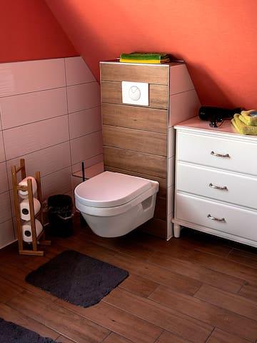 Modernes Badezimmer mit Tageslicht und Blick ins Grüne.