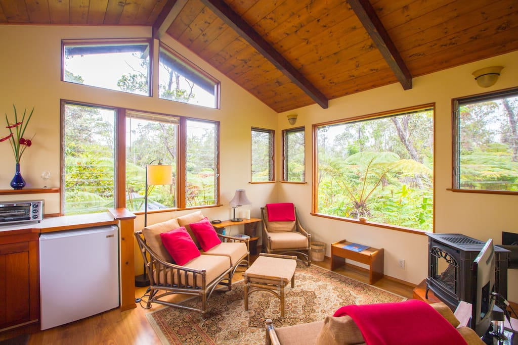 Sitting room with talk open beam ceiling and lots of big picture windows to enjoy nature.
