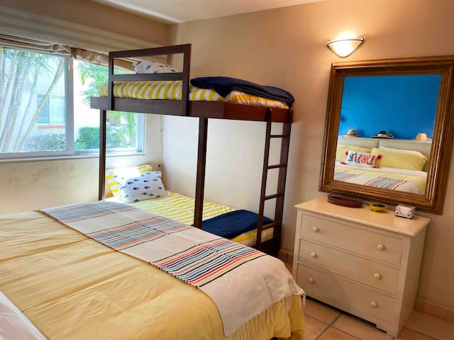This colorful room had a king size bed, two twin bunks, a dresser and closet with drawers and hangers.
