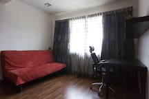 Master Bedroom: The red sofa bed that can be converted into another bed if required.