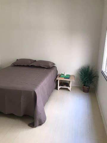 Quarto amplo e iluminado, com uma cama de casal, uma mesa de cabeceira, e cadeiras de apoio