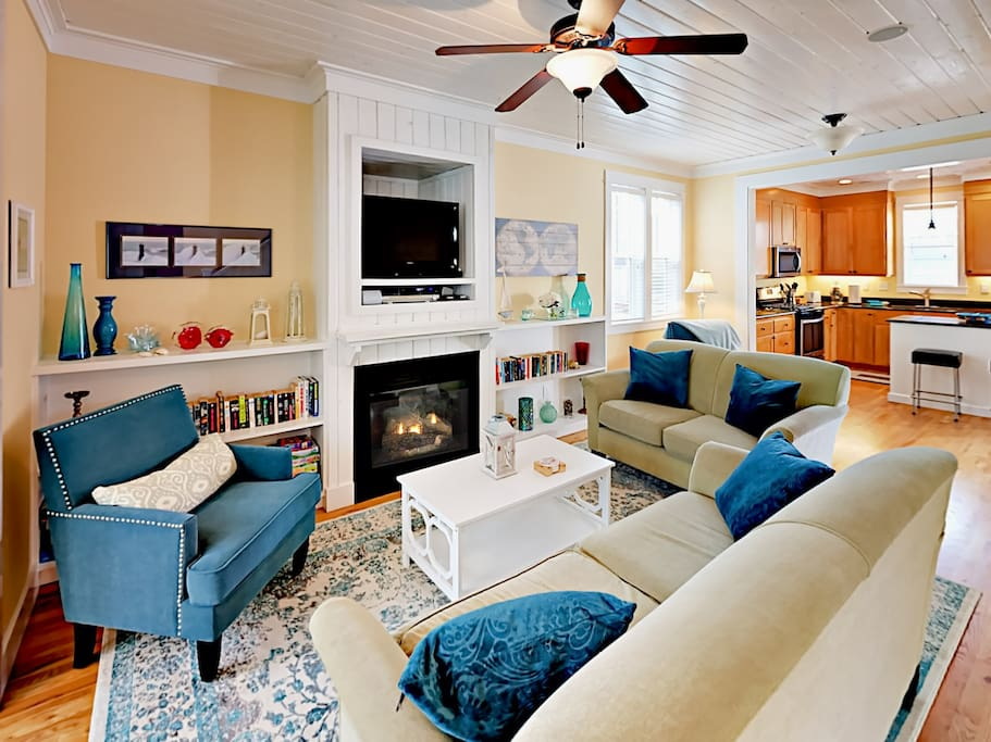 The main living area features a natural gas fireplace surrounded by 2 sofas and a cozy accent chair.