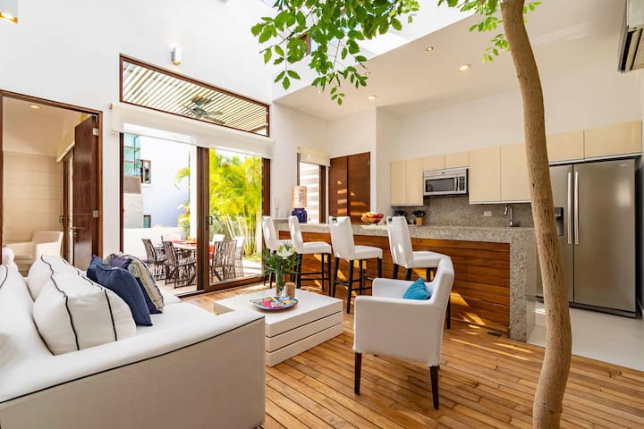 Open space, wooden floor, a beautiful tree inside your living room!
