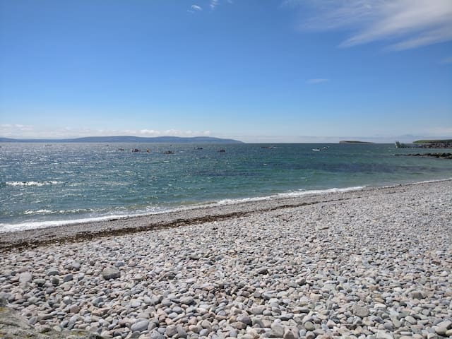 Salthill beach with Black Rock Diving Tower and Bearna Cliffs visible in the distance