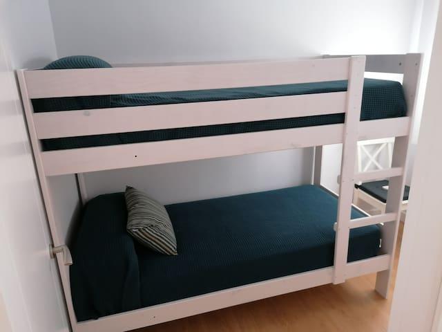 Vista del dormitorio auxiliar, con cama doble, litera