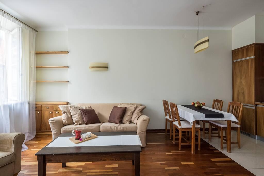 Widok na rozkładaną sofę oraz stół