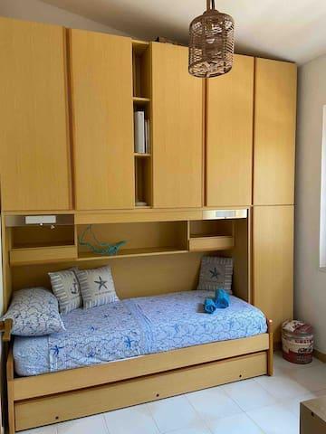 Camera con 1-2 letti singoli, cassettiera e grande armadio