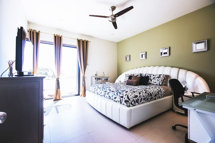Master bedroom with SmartTV, Desk, and Huge walk-in closet/bathroom and a patio door to the outside. Ceiling Fan and individually controlled Air Conditioning keep the room comfortable.