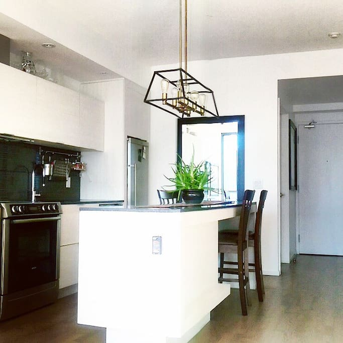 This unit features a stunning mid-century modern kitchen that is fully equipped for your convenience.