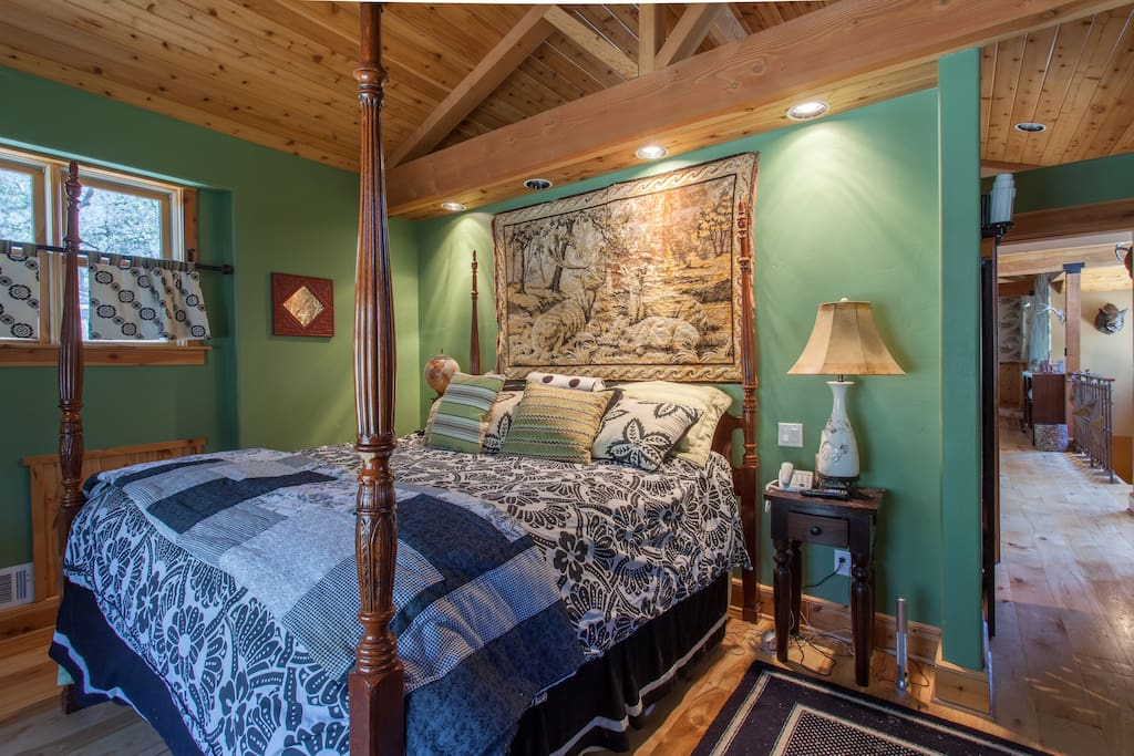 Master bedroom with a king size bed and a large window with beautiful views.