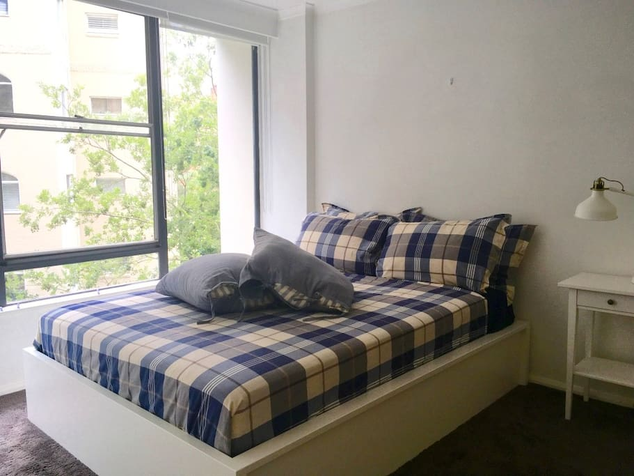 Bedroom with queen bed and blackout blinds