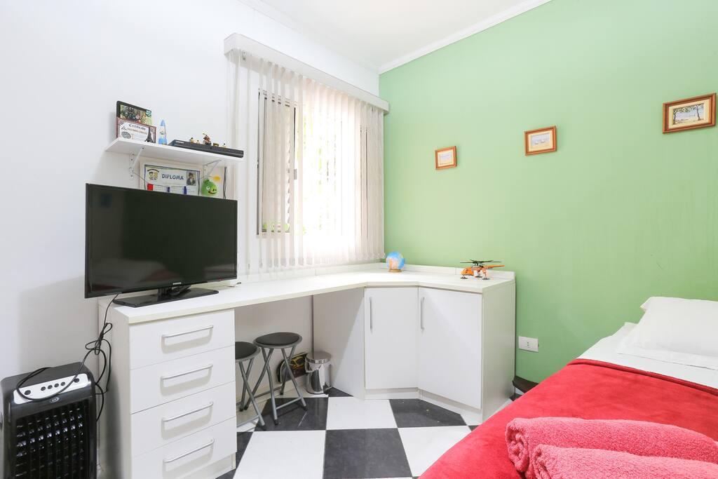 Quarto de solteiro com duas camas (principal + auxiliar). TV com Netflix, ventilador e ótima iluminação.