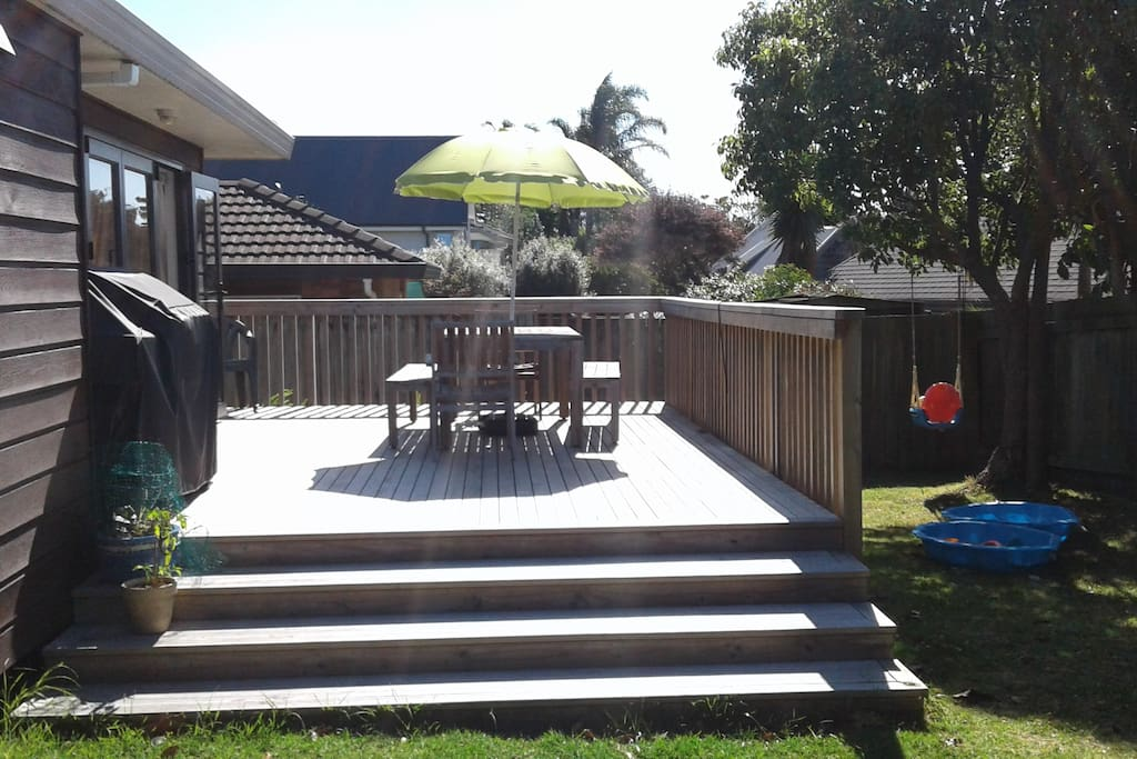 Large sunny north facing deck with BBQ and outdoor table and chairs.