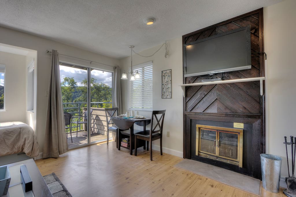 """Open floor plan: Dining Area, Wood Burning Fireplace, 42"""" TV above"""