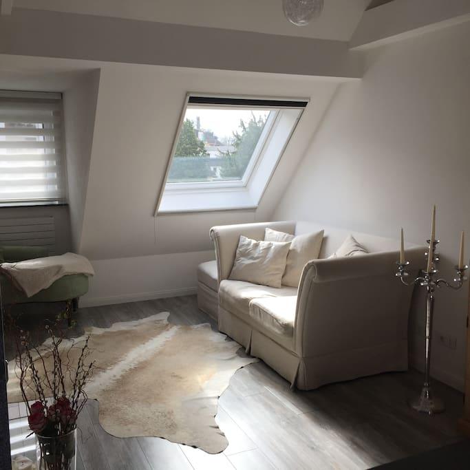 Bequemes Sofa, das durch Fußhocker verlängert werden kann und zu Abenden vor dem Kamin einlädt.