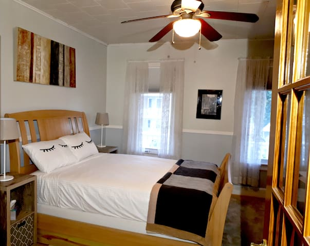 Bedroom has a ceiling fan and 6 foot windows with blackout shades.