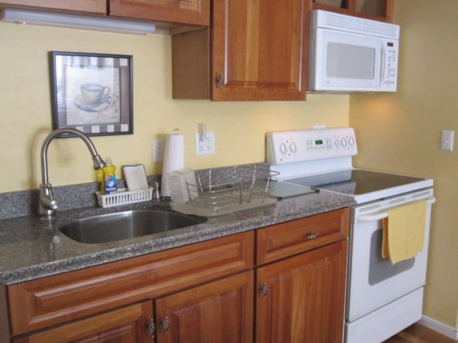 Efficient kitchen offers granite counters and up to date pots, pans and utensils.