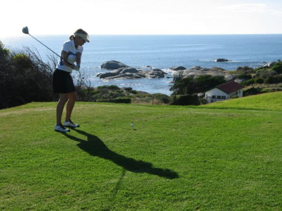 Lady golfer on the 4th Tee Box with Windmill Beach below. Stroll across the road to the course.
