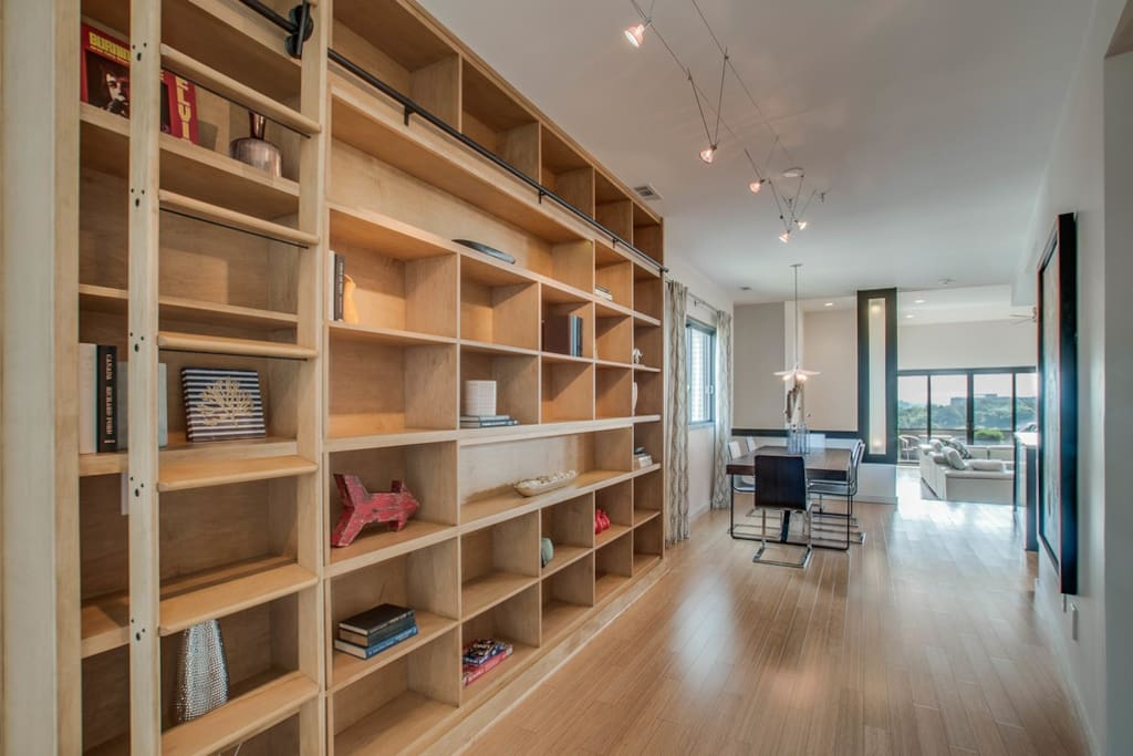 An airy, shelf-lined entryway leads right to the open concept gathering space.