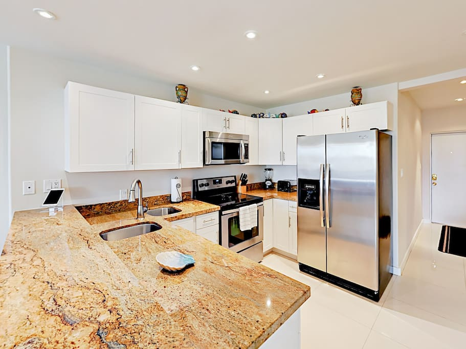 The spacious kitchen with granite countertops and stainless steel appliances.