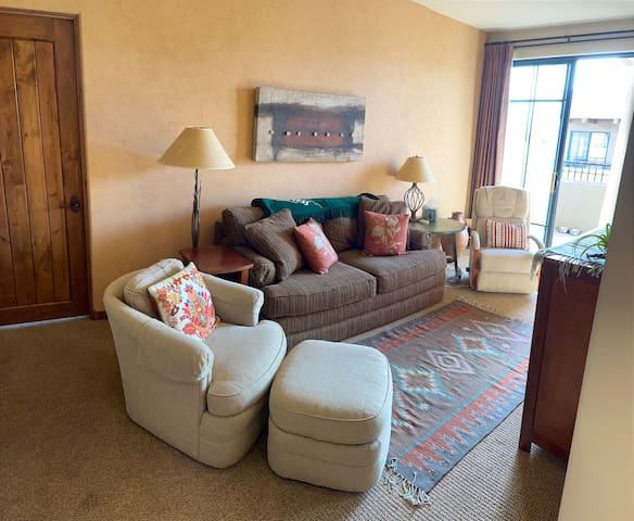 Living Room with recliner, sofabed, and chair with ottoman, Smart TV.  Balcony access.