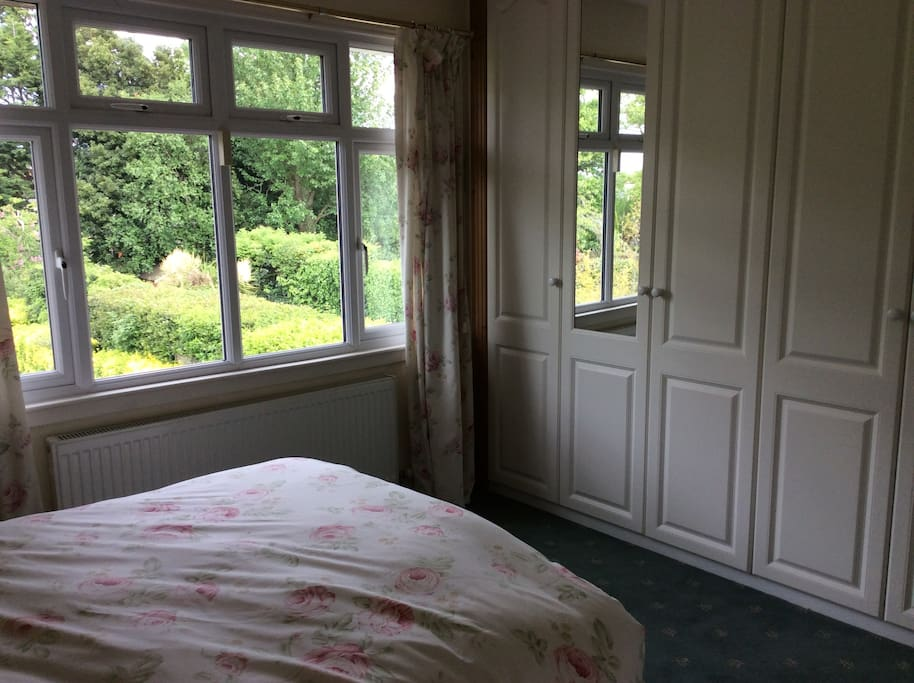 Photo of the bedroom showing the garden & wardrobes. Comfortable double bed